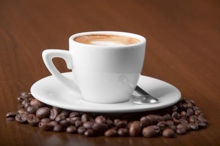 Coffee macchiato surrounded with espresso coffee beans...