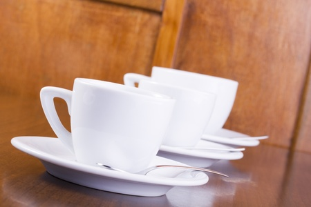 Three coffee cups in a row, served on wooden table