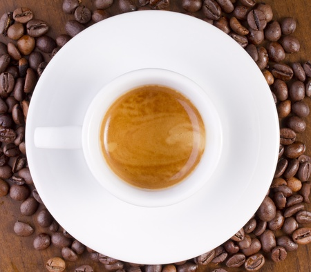 Espresso on coffee beans in white cup. Focus in on coffee Stock Photo