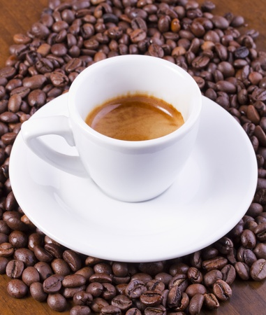 Hot espresso on coffee beans laying on brown table Stock Photo