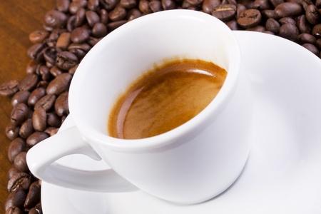 Espresso Espresso mit Kaffeebohnen auf braun Tisch umgeben