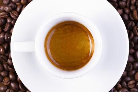 Short espresso in weißen Tasse mit Kaffeebohnen umgeben Lizenzfreie Bilder