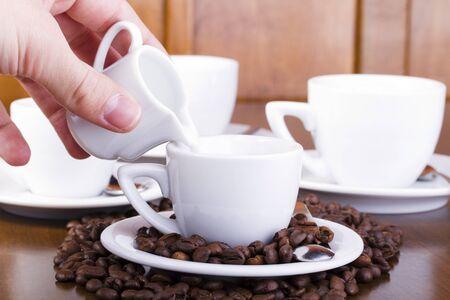 Gießen Sie die Milch in eine Tasse mit heißem Espresso gefüllt