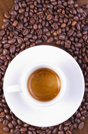 Eine Espresso-Kaffee auf braunen Tisch mit Kaffeebohnen umgeben