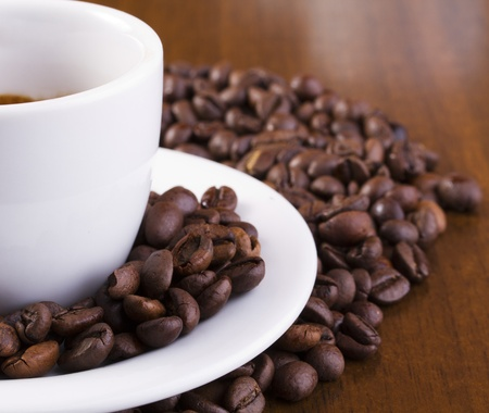 Showing only half of espresso cup surrounded with coffee beans Stock Photo