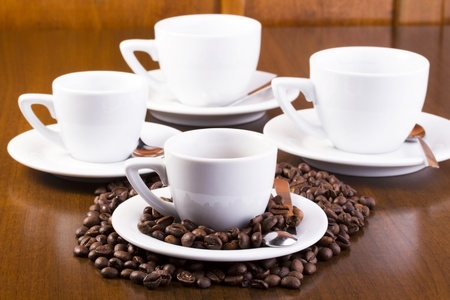 Four espresso cups on wooden table. First one is surrounded with espresso coffe beans