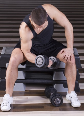 male torso: Exercising with weights while sitting on stepper in the gym Stock Photo