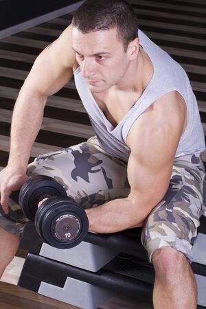 Fitness instructor sitting and weightlifting Stock Photo