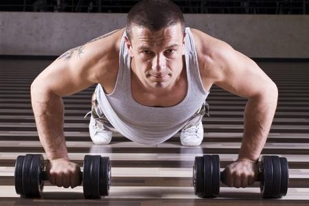 Liegestütze trainieren während er sich über Gewichte