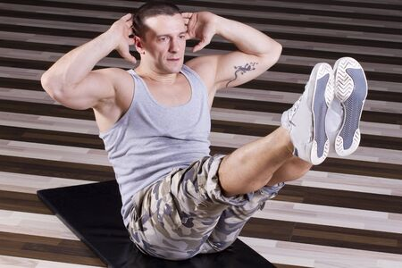 Fitness instructor doing Heavy abs exercise on the floor of the gym Stock Photo