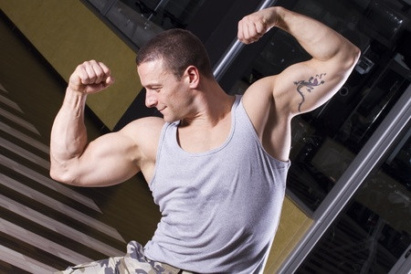 Fitness instructor posing in the gym, showing his muscles Stock Photo