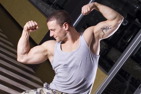 Fitness Instruktor posiert in der Turnhalle, zeigt seine Muskeln