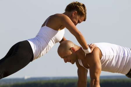 Couple practising on the early morning sun. Girl doing pushups while leaning on a man