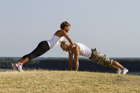 Male and female practising in nature. Beautiful view in background. Stock Photo