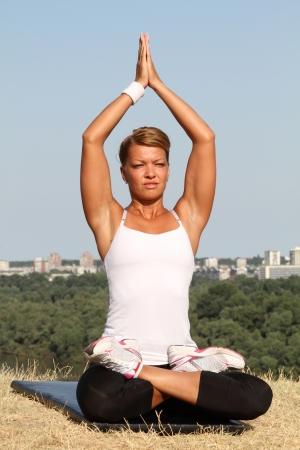 Frau macht Yoga auf einer frühen Morgensonne.