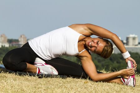 Smiling while doing heavy exercises. Shot taken outside on an early morning sun. Stock Photo