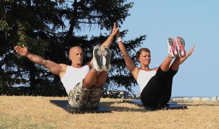 Männliche und weibliche Yoga-Lehrer üben in der Natur