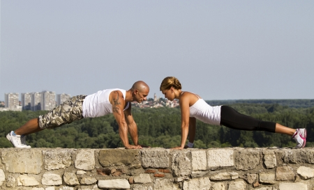 Fitness instructors doing pushups on an old stone wall. Beautiful view in background