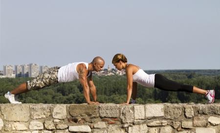 Fitness-Trainer zu tun Liegestütze auf einer alten Steinmauer. Schöne Aussicht im Hintergrund Lizenzfreie Bilder