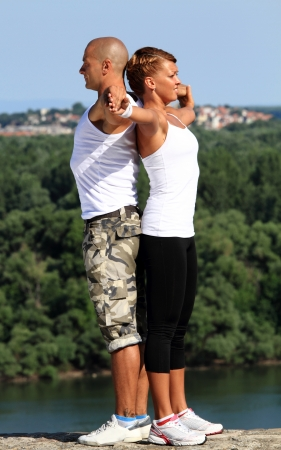 Female and male couple of fitness instructors showing their knowlegde on the top of high stone wall  Beautiful view and background