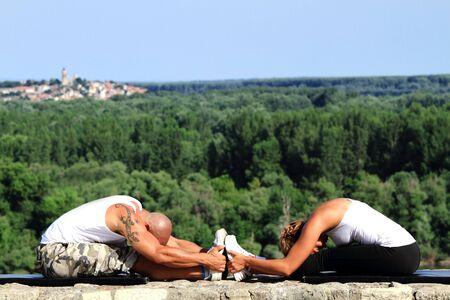 Männliche und weibliche Fitness-Trainer üben in der Natur Doing Stretching-Übungen