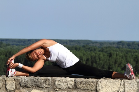 Girl doing stretching exercise on a old stone wall  Beautiful background