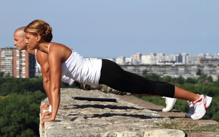 Female and male fitness instructors doing pushups on the top of the stone wall  Stock Photo