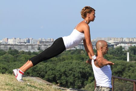 Female and male yoga instructors practising in nature   Stock Photo
