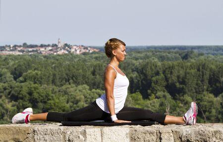Mädchen workingout auf Steinmauer Schöne blaue Himmel im Hintergrund und einen tollen Ausblick