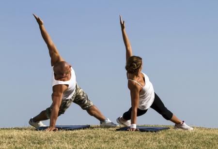 протяжение: Пара делает йогу в природе Красивая Голубое небо на заднем