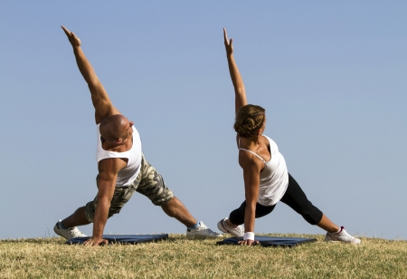outdoor activities: Couple doing yoga in nature  Beautiful blue skies in bacground