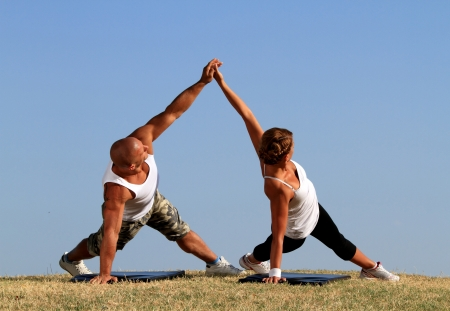 Couple doing yoga. Beautiful blue skies in background. Stock Photo