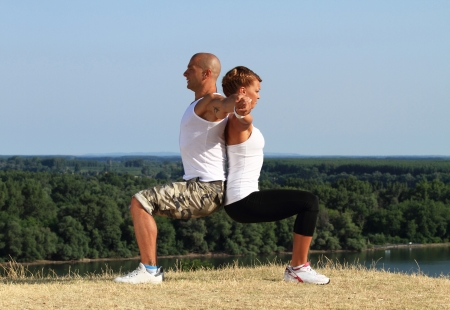 Couple practising yoga. Beautiful blue skies and river Danube in bacground.