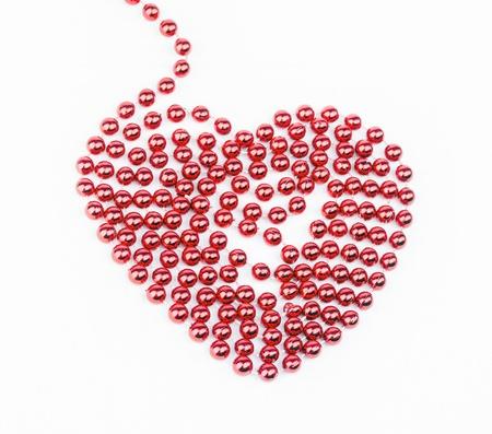 Rotes Herz aus Perlen auf weißem Hintergrund gemacht