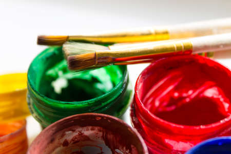 oil can: jars with water color paints and brushes on a white background