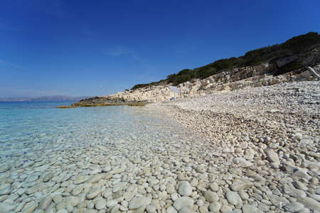 Beach on the island of Proizd, near Vela Luka in Dalmatia, Croatia. The islet of Proizd is known for its crystal clear sea and beautiful beaches. This is a popular tourist destination.