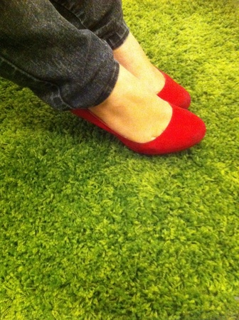 carpet grass: Beautiful red shoes resting on green carpet grass