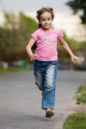 nina corriendo: Niña en los ajustes al aire libre