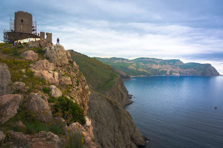 young man stands on the edge of the abyss looking in the distance the sea. Crimea. On the background of the ancient fortress