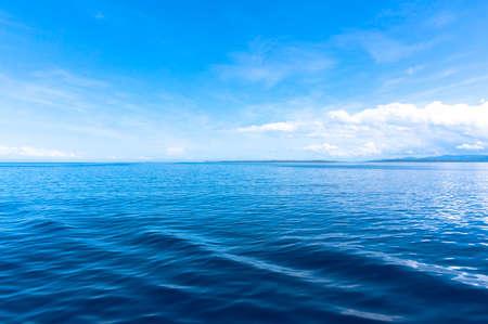 blauwe zee blauwe lucht horizon met witte cumulus wolken