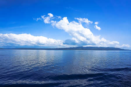 blue sea blue sky horizon with white Cumulus clouds Banco de Imagens