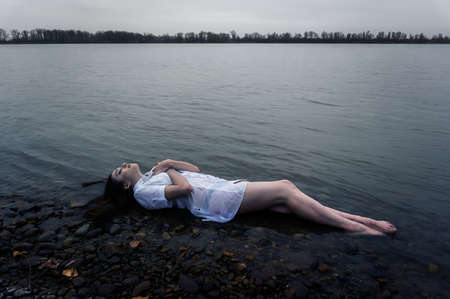 girl lying on the rock of dark river . Ophelia conceptual
