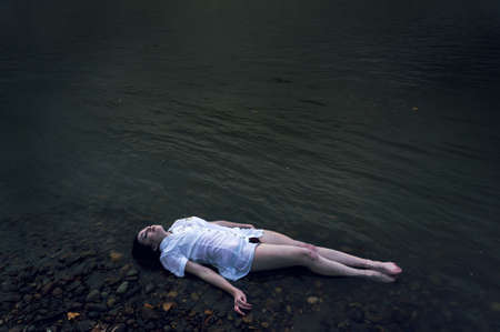 Floating girl lying on the rock of dark river . Ophelia conceptual