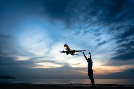 a man stands on the beach and stretches his hands to the airplane flying above him, in the evening on a beautiful sunset on the sea background
