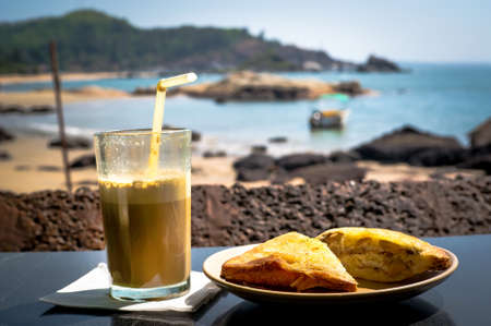 Breakfast on the beach. A sandwich and a coffee cocktail on the table in the restaurant on background of the sea on a hot Sunny day.