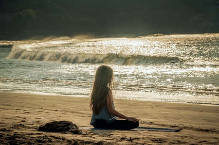 young woman yoga meditation on sunset beach. Gokarna, India