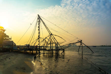 chinese fishing nets: Chinese fishing nets on the shore of the Arabian Sea. Fort Cochin, Kerala, India. Historic Landmark. Warm evening. Scenic contours in the sunset twilight. Bright solar disk. Delicate juicy colors.