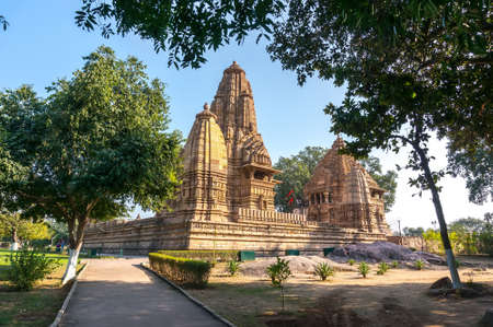 Old Hindu temple, built by Chandela Rajputs, at Western site in Indias Khajuraho framed by trees. White grey for the younger and older beige structure against blue skies over green grass.