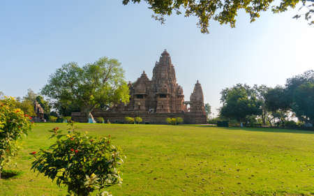 Old and younger Hindu temple, built by Chandela Rajputs, at Western site in Indias Khajuraho framed by trees. White grey for the younger and older beige structure against blue skies over green grass.