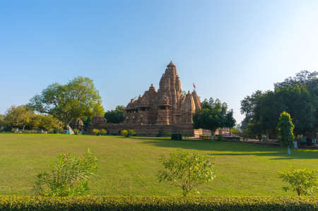 Hindu temple, built by Chandela Rajputs, at Western site in Indias Khajuraho during sunrise. The early morning sun turns decorations stacked on top of each other warm red.